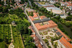 Das Hotel Residenzschloss Bamberg aus der Luft. Gut zu sehen sind der Barockgarten und die schöne Lage an der Regnitz und die Nähe zur örtlichen Konzert- und Kongresshalle. © Welcome Hotels, BU: Stefan Pribnow