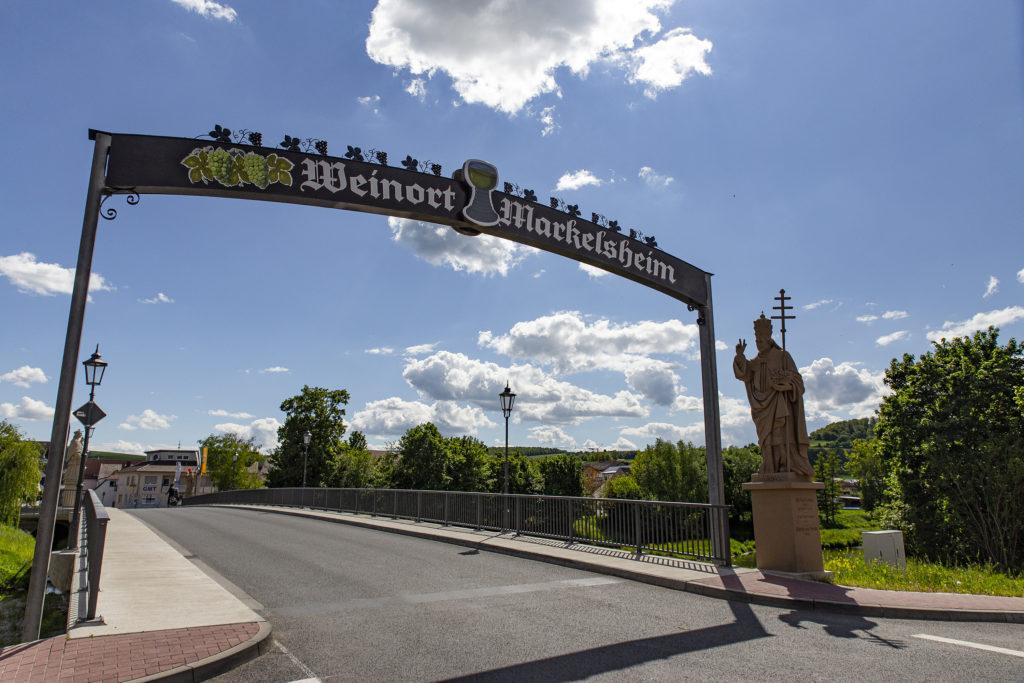 Der Torbogen und der Heilige Urban an der Brücke über die Tauber heißen in Markelsheim willkommen.