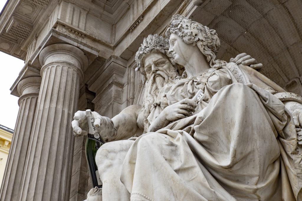 Vor der Albertina: Der Albrechtsbrunnen – ein Spaßvogel hat Danubius mit einer Magnumflasche Champagner ausgestattet